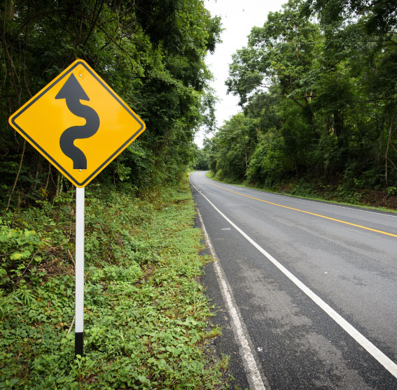Green road with a caution sign for oncoming traffic