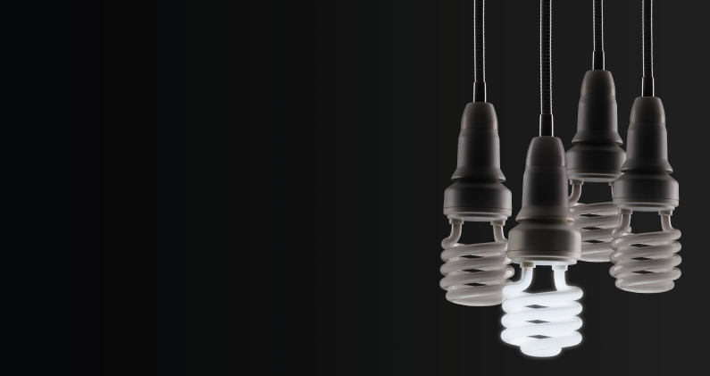 4 light bulbs side by side with one lit on black background
