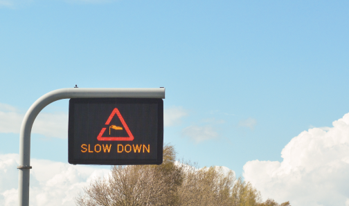 slow down wind traffic sign above road